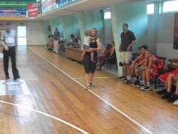 Треньорка води мач с дете в ръце